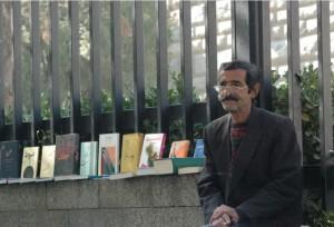 قاسم امیری، شاعر و نویسنده (در کنار آرامگاه بوعلی کتاب میفروشد).